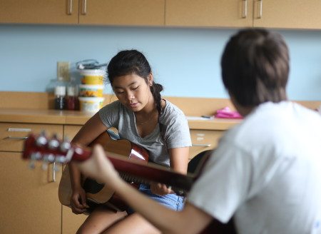 Two guitarists are in the midst of a conversation while they practice their chords. The students are able to learn quickly in this friendly environment.