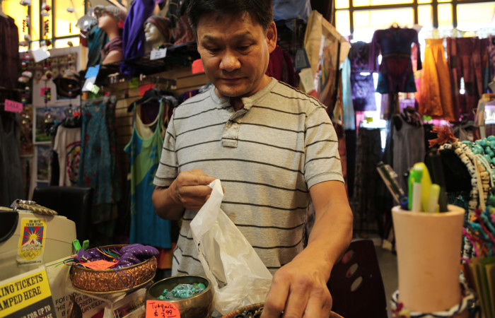 Ngawang Dakpa, owner of Tibet Arts & Gifts LLC, bags his merchandise in plastic for one of the last times due to the recent ban on plastic bags.