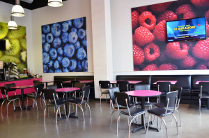 The interior of Chilly Billy's, located in Dinkytown, is decorated with large fruit pictures and brightly colored pink tables.