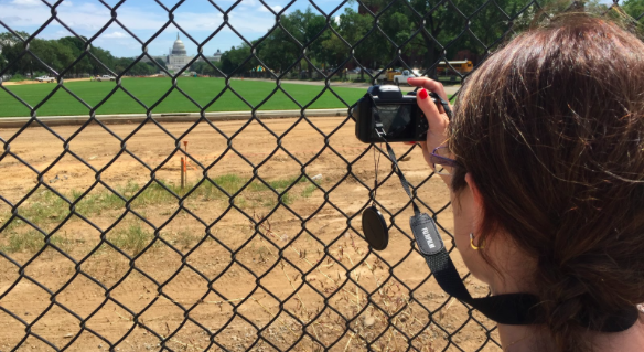 Sandra Caneca of Portugal takes a photo of the Capitol building through a fence