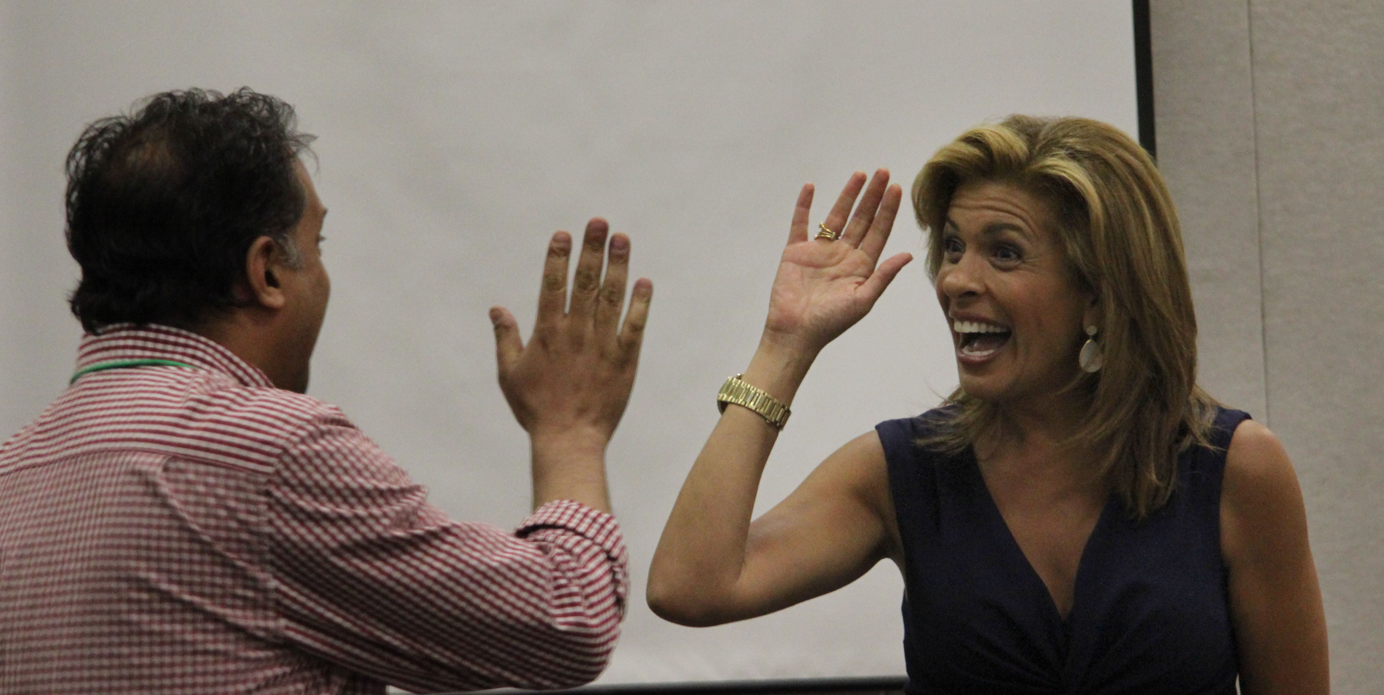 Hoda Kotb of the Today Show high-fives with Star Tribune television critic Neal Justin at JCamp, a summer camp for aspiring high school journalists. (Jack Chen/JCamp Live Photographer